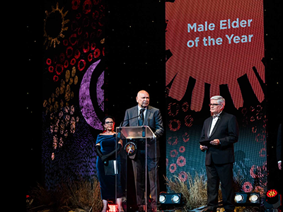 Two men and one woman stand on a stage. They are all wearing formal attire. One man is standing at a lectern. A screen in the background reads: Male Elder of the Year.