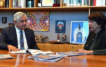 Joint Council on Closing the Gap Co-chairs Minister for Indigenous Australians, the Hon Ken Wyatt AM, MP and Pat Turner AM sitting at a meeting table with papers on the table. In the background is a bookshelf with Indigenous artwork and books.