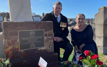 A man wearing a tie and black coat with military medals, and a woman in a black dress kneel next to a grave site. The grave is adorned with bouquets of flowers and has a plaque identifying it as that of Jack Alick Bond, a veteran of the Boer War.