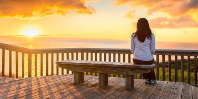 Person sitting on a bench watching a sunset