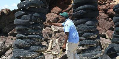A man under a bridge and surrounded by rocks is standing between two towers built of used car tyres. The man is leaning over to the one of the tower of tyres and is holding a yellow tool in his right hand. The man is dressed in a blue shirt and wearing a green baseball cap.
