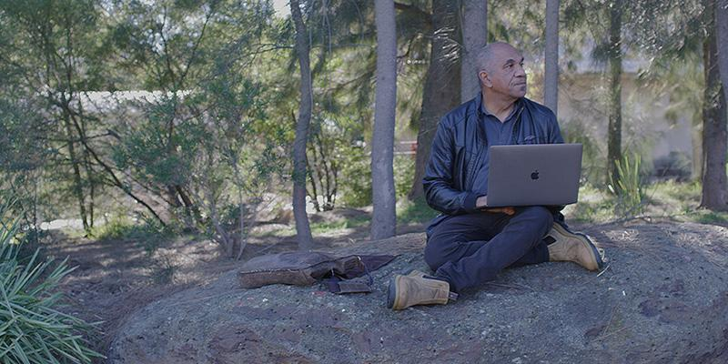 A man sits cross-legged under some trees in an Australian bushland setting. There is a body of water behind him, which can be seen between the trees. An open laptop computer rests on one knee.