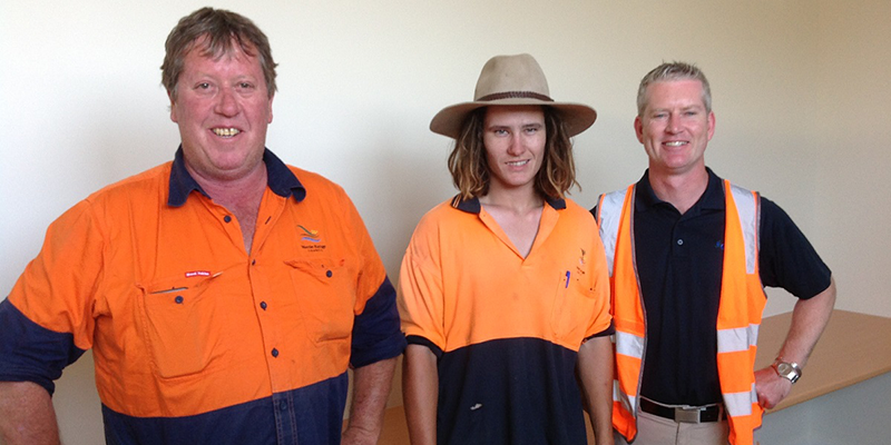 Three men stand wearing predominantly orange work wear. The one in the middle is younger and wears a broad brimmed hat.
