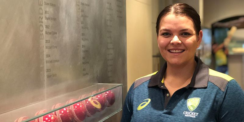 Image of Courtney Hagen. She is smiling while standing next to a memorial cricket wall.