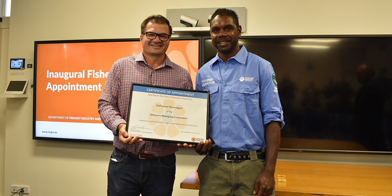 Two men stand side by side and hold between them a large framed certificate. The man on the left wears a checked shirt and dark trousers. The man at right wears a blue shirt and green trousers. They stand in a room with two large TV screens in the background.
