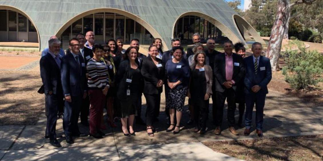 Twenty-three Indigenous leaders from the public services across Australia and New Zealand pose for a picture in front of the Shine Dome in Canberra, Australia