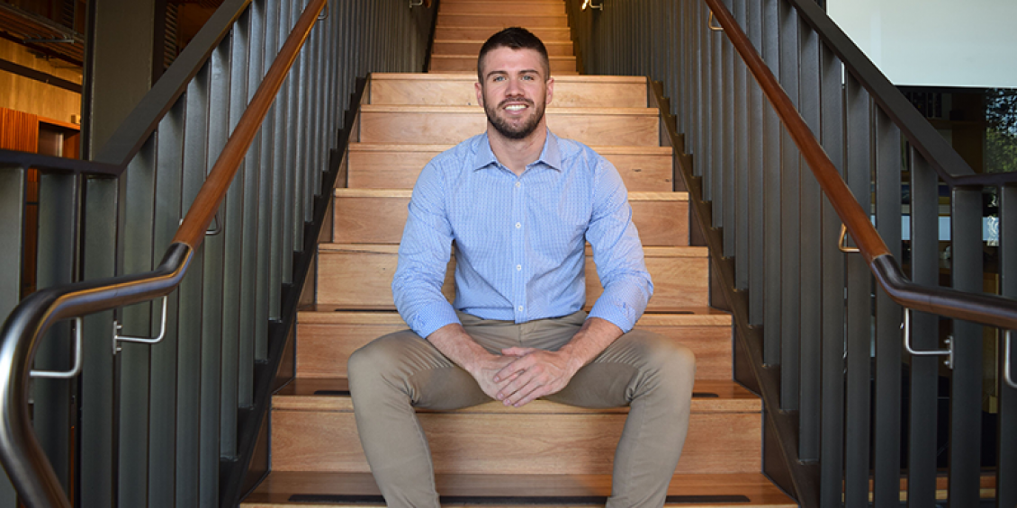 Image of Peter Honeyman smiling, sitting on a staircase