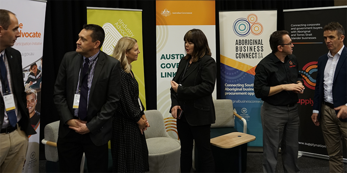 Six people standing and talking at a trade fair. They are wearing business attire.