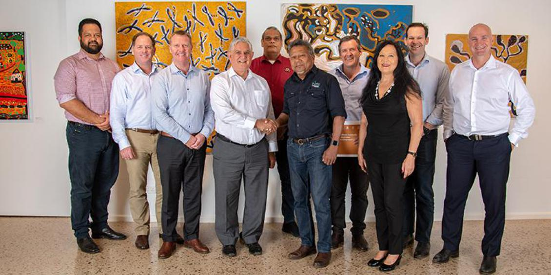 Minister Wyatt and Minister Canavan with the Indigenous Reference Group. There are nine men and one woman pictured, all wearing smart casual clothing, standing in front of colourful Indigenous artwork