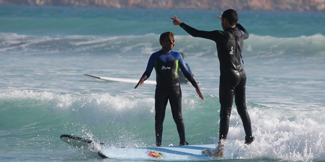 Two indigenous youths surfing on a beach